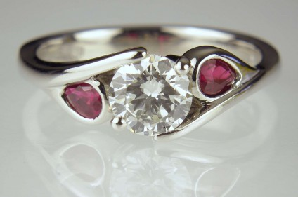 Diamond & ruby ring - 0.7ct round brilliant cut diamond G colour SI1 clarity with GIA certificate, set with pair of pear cut rubies in platinum