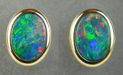 Opal doublet earstuds in 18ct yellow gold - Vibrant multicoloured opal doublet oval pair weighing 1.32ct, rubover set in 18ct yellow gold. Earstuds are 7x9mm