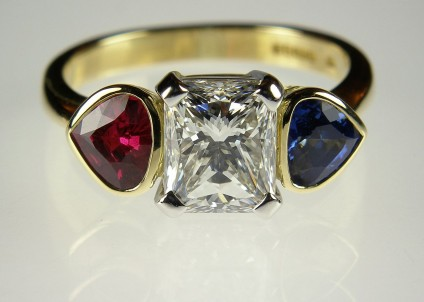 Radiant cut diamond ring with ruby & sapphire flanking stones - 2.03 carat radiant cut diamond H colour VS1 clarity set with fine matching shield cut ruby and sapphire of 60 points each in platinum and 18 carat yellow gold.