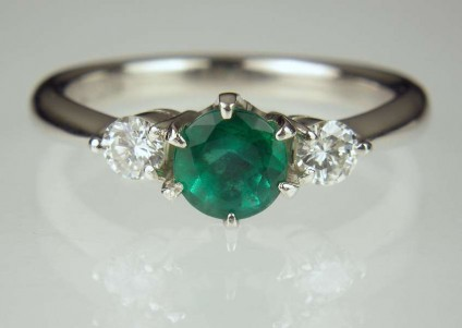 Emerald & Diamond Ring - 0.65ct emerald round set with a matched pair of 0.20ct round brilliant cut diamonds in platinum