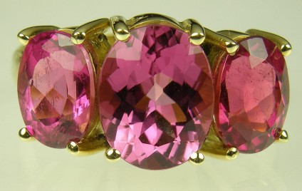 Pink Tourmaline Ring - Pink tourmaline 3 stone ring set in 18 carat yellow gold.  Central stone 8 x 10mm