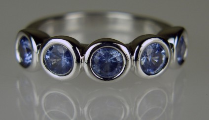 Pastel blue sapphire rubover set five stone ring - Pretty pastel sapphire ring set with five round sapphires totaling 2.65ct in weight, each sapphire is 5mm in diameter, rubover set in 18ct white gold. Ring size P. This ring is secondhand, as is reflected in the modest price. It has been checked, re-polished and re-rhodium plated by Just Gems and comes with our usual 6 month warranty.