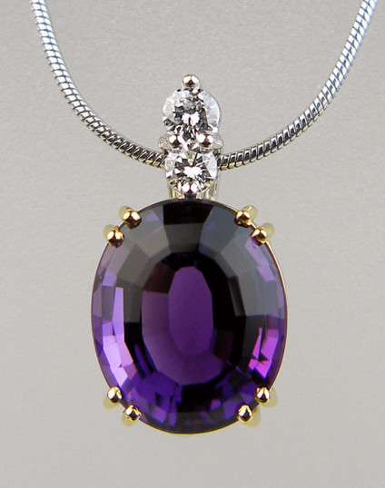Amethyst & diamond pendant in 18ct yellow and white gold - Exquisite oval amethyst set in 18ct yellow gold with a diamond set bail in 18ct white gold and suspended from an 18ct white gold chain. Pendant is secondhand. This top quality piece has been checked by our gemmologist and jeweller and comes with a 6 months Just Gems warranty. Pendant is 19x10mm.