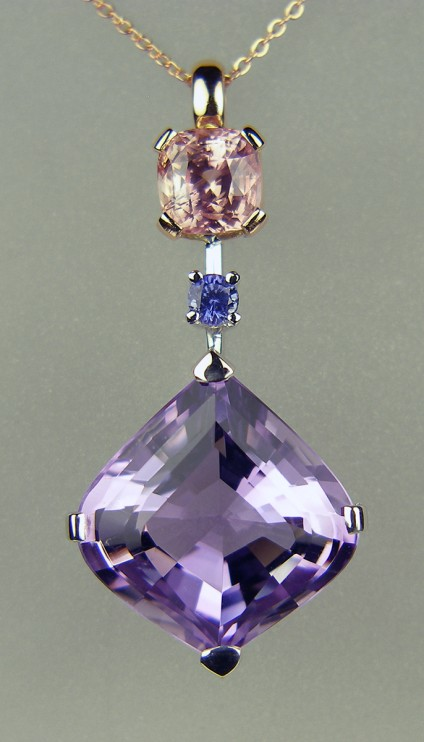 Amethyst & sapphire pendant in rose & white gold - Beautiful onion cut amethyst (cut in Idar Oberstein) set with 0.22ct round natural blue sapphire, both set in 18ct white gold. Also set with a delicate peachy pink 2.85ct cushion cut sapphire mounted in 18ct rose gold. Perfect with either a white or rose gold chain. Pendant measures 40mm long and 20mm wide.