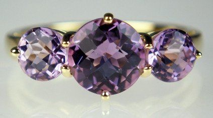 Amethyst three stone ring in 9ct yellow gold - Three round chequerboard (also known as harlequin cut) amethysts set in a 9ct yellow gold ring