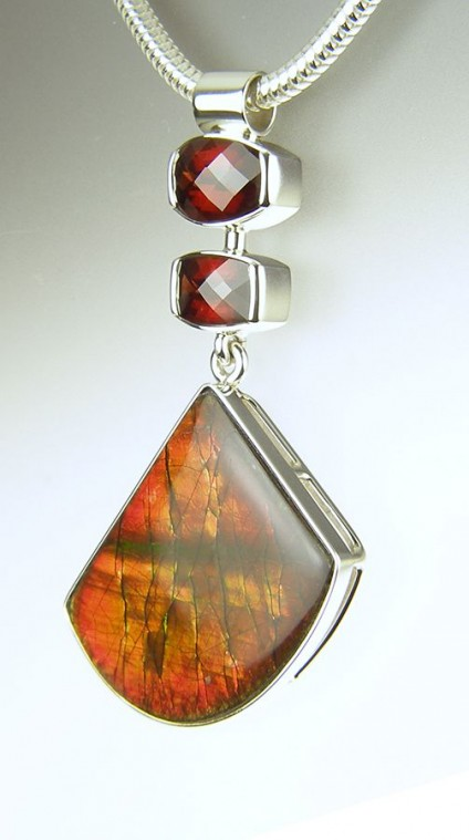 Ammolite & garnet pendant in silver - Ammolite & garnet pendant - ammolite (fossilised ammonite shell from Alberta, Canada) set with African pyrope garnet chequerboard cut weighing 1.66 & 2.45ct, mounted as a pendant in silver.