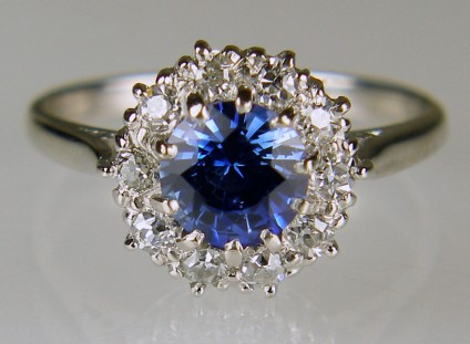Antique style sapphire & diamond cluster ring in 18ct white gold - 1.01ct round cut sapphire in bright blue set with a halo of diamonds totalling 0.50ct and set in 18ct white gold