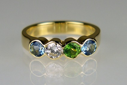 Aquamarine, diamond & green garnet birthstone ring - Delicate ring in 18ct yellow gold set with 0.42ct pair of aquamarines, 0.30ct green garnet and 0.23ct diamond in F colour VS clarity. All gems approximately 4mm in diameter. The stones were chosen because the are the birthstones of the parents and children in a family.