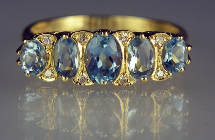 Aquamarine & diamond ring in 18ct yellow gold - Pretty secondhand ring made in an antique style gypsy setting in 18ct yellow gold set with 5 oval aquamarines totalling approximately 2ct and set with 8 x little 16 cut round diamonds totalling about 0.1ct diamond weight. The ring is size O 1/2, and is in excellent condition.