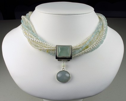 Aquamarine & Pearl Multistrand Necklace - Multi stranded necklace of faceted and rounded polished aquamarine beads; and white freshwater pearls. The necklace can be worn untwisted or twisted to alter the length to the wearer?s choice, outfit and occasion. The necklace is fastened with a larimar and silver clasp.  Larimar is a blue variety of the mineral pectolite.  \r\nThere is a detachable aquamarine and white opal pendant in silver. The pendant contains two cabochon polished aquamarines weighing a total of just over 40 carats.