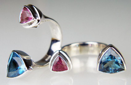 Pink tourmaline & blue topaz between finger ring in silver - Trillion cut pink tourmaline & trillion cut London Blue topaz set in silver 'between finger' ring. The silver is rhodium plated.
