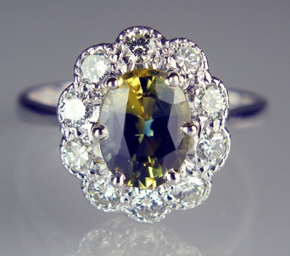 Bi-colour 'Wattle' sapphire & diamond cluster ring in 18ct white gold - Beautiful bi-colour oval cut sapphire from New South Wales, Australia, weighing 2.22ct set with a 0.60ct of white diamonds in 18ct white gold ring.  The sapphire is what is referred to as a 'Wattle' sapphire, named for the yellow flowers and glaucous green leaves of the Australian wattle tree. The stone is actually bi-coloured yellow and blue, the combination of these two colours giving it a lively green flash of colour when the ring is being worn.