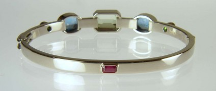 Birthstone bangle reverse view - 18ct white gold bangle set with family birthstones of ruby, aqumarine, blue topaz and garnet