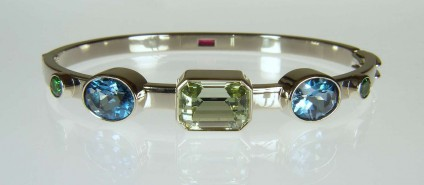 Birthstone bangle - Beautiful bangle made with 5.82ct unheated greenish blue aquamarine emrald cut, 5.78ct pair of oval blue topaz, 0.84ct pair of round brilliant cut green tsavorite garnets and, on the reverse side, a 0.37ct emerald cut Tanzanian ruby. All bezel set in 18ct white gold.