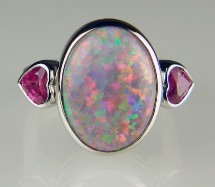 Black opal and pink sapphire heart ring in platinum - 7.73ct oval black solid opal from New South Wales, Australia, set with a 0.93ct pair of bright reddish/pink heart cut sapphires in platinum