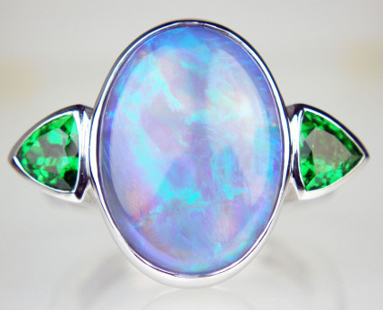 Oval black opal & tsavorite garnet ring - Beautiful strikingly coloured green and blue coloured 6.50ct black opal oval cabochon from Lightning Ridge, Australia rubover set in 18ct white gold and flanked by a 0.94ct matched pair of trillion cut tsavorite garnets, also rubover set. The stones are mounted on a Fingermate opening shank to accommodate larger knuckles and slender fingers. Ring size M.