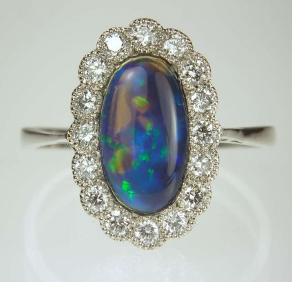 Black opal & diamond ring in platinum - Black opal and diamond cluster ring with 0.32ct f colour VS clarity diamonds.  Mounted in platinum.  Antique ring restored to nearly new condition by Just Gems.