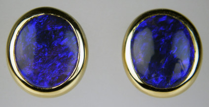 Black opal earstuds in 18ct yellow gold - 3.20ct oval black opals from Lightning Ridge, Australia, rubover set in 18ct yellow gold. Earstuds are 10 x 9mm.