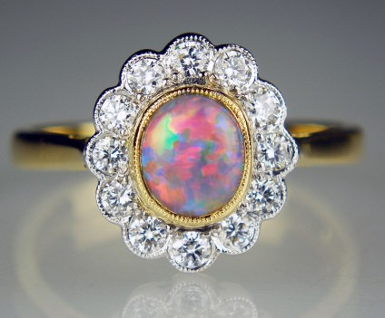 Black opal and diamond halo ring - Beautiful oval cabochon black opal weighing 0.66ct and set with 0.35ct of G colour VS clarity white diamonds in 18ct yellow and white gold ring