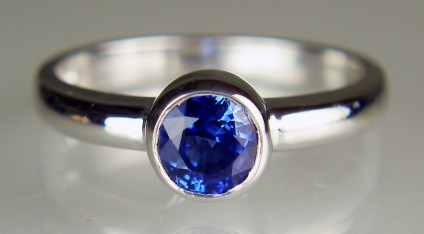 Sapphire ring in 18ct white gold - 6.1mm round  bright blue sapphire weighing 1.34ct rubover set in 18ct white gold ring