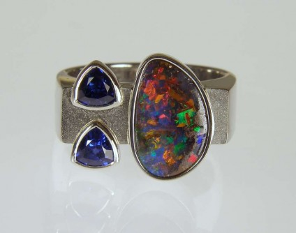 Boulder opal & sapphire ring in palladium - 2.36ct boulder opal from Queensland, set with a 0.65ct pair of trillion cut sapphires, in a polished and frosted palladium ring