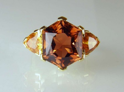 Tourmaline & garnet ring - 9.66ct hexagonal cut deep golden brown tourmaline of exceptional clarity flanked by a 3.07ct matched pair of trillion cut mandarin garnets from Nigeria set in a handmade 18ct yellow gold ring