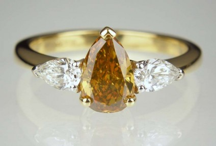 Golden pear cut diamond ring - Golden brown pear cut 1.12ct diamond with Gem-A cert, set with a matched pair of 0.46ct pear cut diamonds in G colour VS clarity, set in 18ct white & yellow gold. The centre diamond in this ring is strongly yellow/green fluorescent and this gives the stone a fabulous colour range that changes with illumination intensity and whether the stone is viewed under artificial or natural light. Just STUNNING!