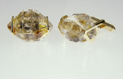 Oil included quartz cufflinks in gold - Cufflinks in 9ct yellow gold, larger crystals. Rare oil included quartz crystals from Balochistan are set in individually handmade gold mounts.  The crystals are approximately 2-3cm in all dimensions and contain golden droplets of light oil, along with darker bitumen and an aqueous solution.  The inclusions fluoresce a strong bluish green under UV light.  Each pair of cufflinks comes with a UV pen torch and an explanation of the crystal.  These crystals are extremely rare and it is difficult to find such perfect examples as sold by Just Gems.  The setting is precisely made to fit each unique crystal and has to be created without the application of heat, which could cause the crystal to fracture.  Each piece is handmade in Scotland and hallmarked in Edinburgh. Pendants and earrings also available.  A selection of crystals are available for bespoke designs.