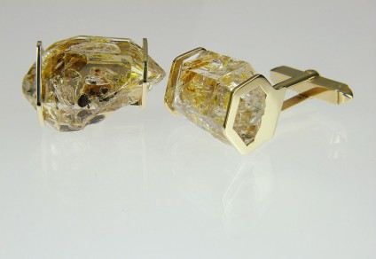 Oil included quartz cufflinks in gold - Cufflinks in 9ct yellow gold, smaller crystals. Rare oil included quartz crystals from Balochistan are set in individually handmade gold mounts.  The crystals are approximately 2-3cm in all dimensions and contain golden droplets of light oil, along with darker bitumen and an aqueous solution.  The inclusions fluoresce a strong bluish green under UV light.  Each pair of cufflinks comes with a UV pen torch and an explanation of the crystal.  These crystals are extremely rare and it is difficult to find such perfect examples as sold by Just Gems.  The setting is precisely made to fit each unique crystal and has to be created without the application of heat, which could cause the crystal to fracture.  Each piece is handmade in Scotland and hallmarked in Edinburgh. Pendants and earrings also available.  A selection of crystals are available for bespoke designs.