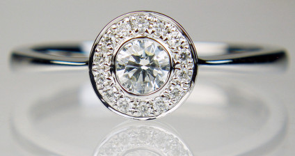 0.30ct diamond rubover halo ring in 18ct white gold - 0.20ct central round brilliant cut diamonds in G colour VS clarity, surrounded by a halo of matching smaller diamonds, total diamond weight 0.30ct, in 18ct white gold