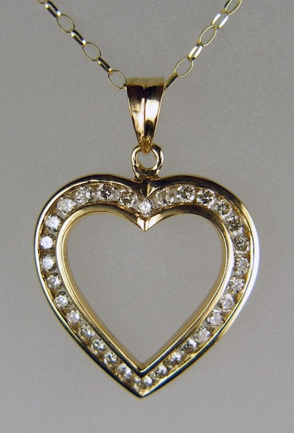 "1ct diamond heart pendant in 9ct yellow gold - 1ct of round brilliant cut diamonds channel set into a pretty heart shaped pendant and suspended from an 18"" 9ct yellow gold chain. Diamonds are I/J colour and VS clarity. Pendant measures 24mm wide by 34mm long. The piece is secondhand but in 'as new' condition."