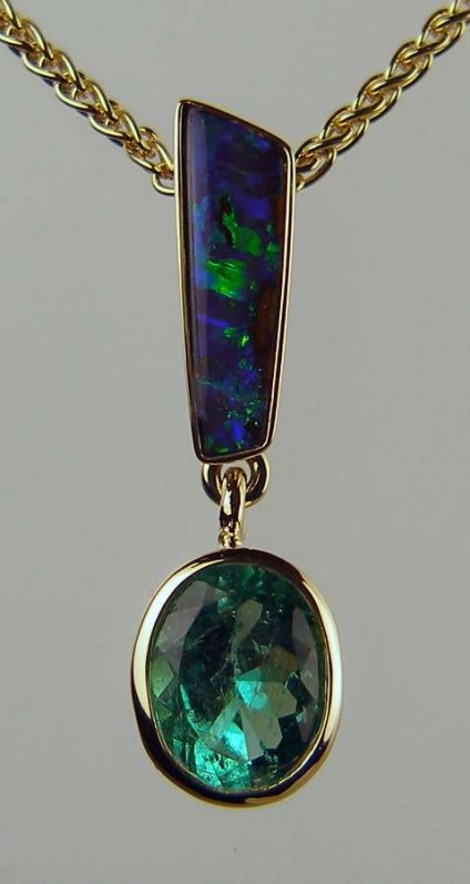 """Emerald & Opal Pendant - Oval Colombian emerald rubover set in 18ct yellow gold and suspended from a fine sliver of blue/grey Australian boulder opal, mounted on an 18"""" 18ct yellow gold spiga chain"""