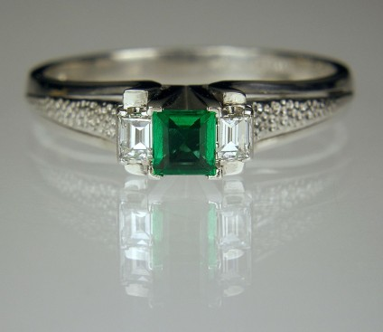 Emerald & diamond ring in platinum - Emerald & diamond ring in platinum. 10pt Colombian emerald flaked by 2 x 5pt baguette cut diamonds. Head 7 x 4mm.