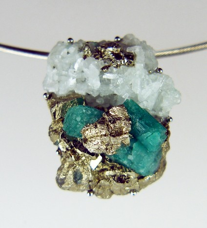 Rough emerald pendant in palladium - Colombian emerald mineral specimen, rough and unpolished, set in simple palladium claw mount and suspended from stainless steel cable