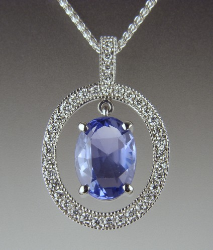 Sapphire & Diamond Pendant - Customer's pale blue Sri Llankan sapphire set in diamond set frame pendant in 18ct white gold.  The sapphire moves within the mount to allow maximum sparkle from a shallow stone.  The sapphire was not sourced by Just Gems
