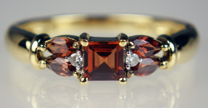 Garnet & diamond ring in 9ct yellow gold - Garnet round and marquise cuts weighing 0.73ct and set with 2 points of round brilliant cut diamonds, mounted in 9ct yellow gold. A very lovely ring.
