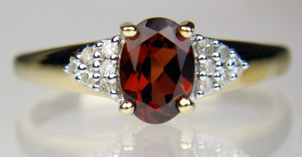 Garnet oval ring with diamond cluster shoulders in 9ct yellow gold - Garnet oval, strong bright red, flanked by a cluster of round brilliant cut diamonds on each shoulder, ring in 9ct yellow gold