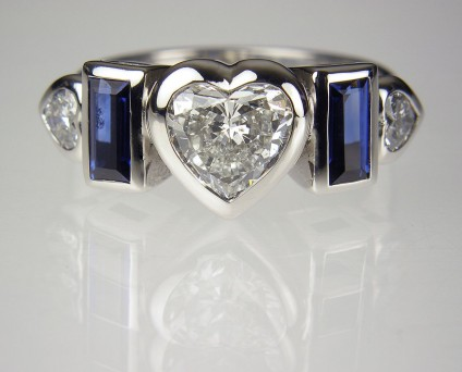 Diamond & sapphire ring in gold - Lady's dress ring in 18ct white gold set with a central 0.91ct heart cut diamond, F colour SI1 clarity, flanked by a matched pair of heart cut diamonds totalling 0.22ct and a matched pair of blue sapphire baguettes totalling 0.6ct.