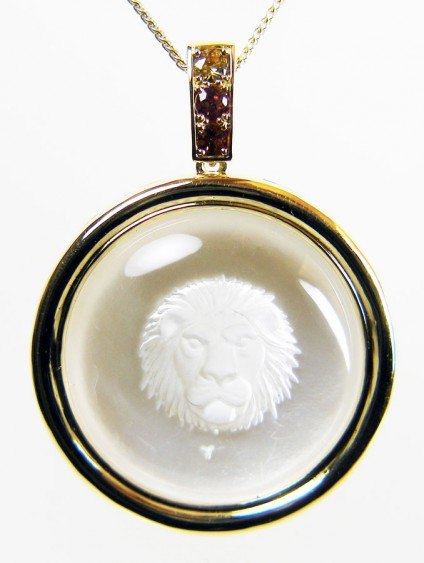 "Leo pendant in rock crystal & 18ct yellow gold - Lion's head of Leo, exquisitely carved into a dome of pure rock crystal by renowned German engraver Erwin Pauly, set against a subtly shimmering background of polished mother-of-pearl and mounted in 18ct yellow gold with a line of golden Kenyan sapphires weighing 0.52ct.  Pendant is suspended from an 18"" yellow 18ct gold chain. Pendant is 50mm long and 36mm wide."