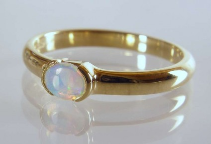 Opal Ring - 0.18ct white opal with vivid green and blue colour flashes set in 18ct yellow gold