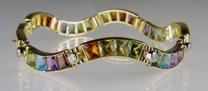 Gemset bracelet in 18ct white & yellow gold - 17.72ct of wedge cut coloured gemstones, set with 1.23ct diamonds in 18ct yellow and white gold. A stunning and unique bracelet. Coloured gemstones are peridot, citrine, garnet, tourmaline, amethyst and blue topaz.