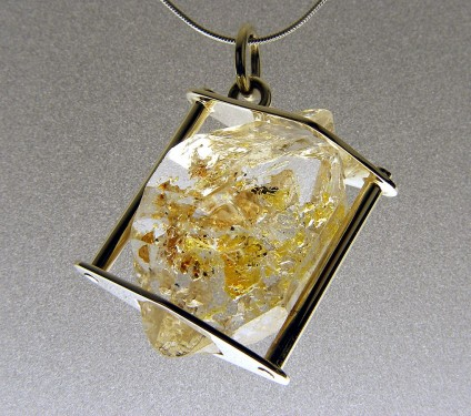Oil included quartz pendant in gold - Oil included quartz crystal pendant set in 9ct white gold with chain.  Rare oil included quartz crystals from Balochistan are set in individually handmade white gold mounts.  The crystals are approximately 2-3cm in all dimensions and contain golden droplets of light oil, along with darker bitumen and an aqueous solution.  The inclusions fluoresce a strong bluish green under UV light.  Each pendant comes with a UV pen torch and an explanation of the crystal.  These crystals are extremely rare and it is difficult to find such perfect examples as sold by Just Gems.  The setting is precisely made to fit each unique crystal and has to be created without the application of heat, which could cause the crystal to fracture.  Each piece is handmade in Scotland and hallmarked in Edinburgh. Matching earrings are available. Also Cufflinks.  A selection of crystals are available for bespoke designs.