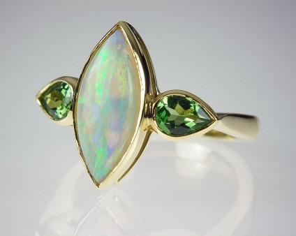 Opal & tsavorite garnet ring in gold - Opal & green garnet ring - Ring set with 1.33ct light opal and a pair of pear cut tsavorite garnets in 18ct yellow gold.