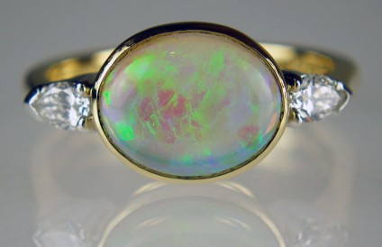 Opal and diamond ring in yellow gold - 1.59ct oval opal cabochon set with 0.21ct pear cut white diamonds in platinum and 18ct yellow gold.