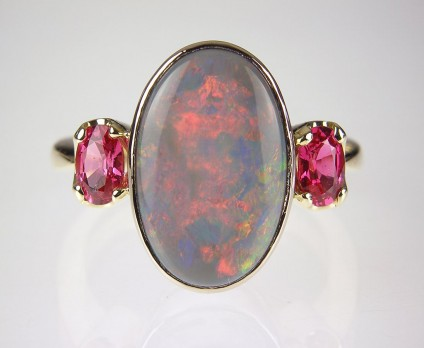 Black opal & Mahenge spinel ring in gold - Opal & red spinel ring - Ring set with 3.4ct oval black opal and a pair of oval cut Mehenge spinels in 18ct yellow gold.