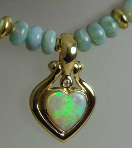 Opal Heart Pendant on Larrimar Beads - Cabochon heart cut solid opal from Australia, set with a diamond in 18ct yellow gold as pendant/enhancer on a necklace of 18ct yellow gold and larrimar beads