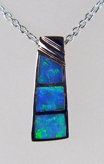 "Inlaid black opal pendant in silver - Pretty silver pendant inlaid with Australian solid black opal. The pendant has been rhodium plated to resist tarnishing and is suspended from a rhodium plated silver chain of adjustable length 15-22""."
