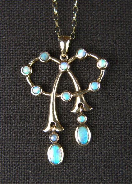 "Opal pendant in 9ct yellow gold - Delicate and pretty opal pendant set with 8 x 2.5mm round solid white opals and two pairs of oval/round opals as moving drops to the tails of the bow. This is an antique piece but has, at some time in the more recent past, been hallmarked as 9ct. The piece measures 27mm wide by 40mm long and is suspended from a fine 9ct 21"" gold chain."