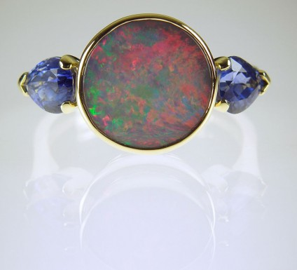 Black opal & sapphire ring - Opal and sapphire ring in 18ct yellow gold.  Round 1.45ct opal cabochon with red, green and blue colours, bezel set and flanked by a 1.55ct matched pair of sapphire pear cuts.