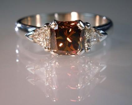 Coloured & white diamond ring in platinum - 1.45ct radiant cut fancy deep orange brown diamond set with 0.41ct trillion cut white diamonds in platinum.